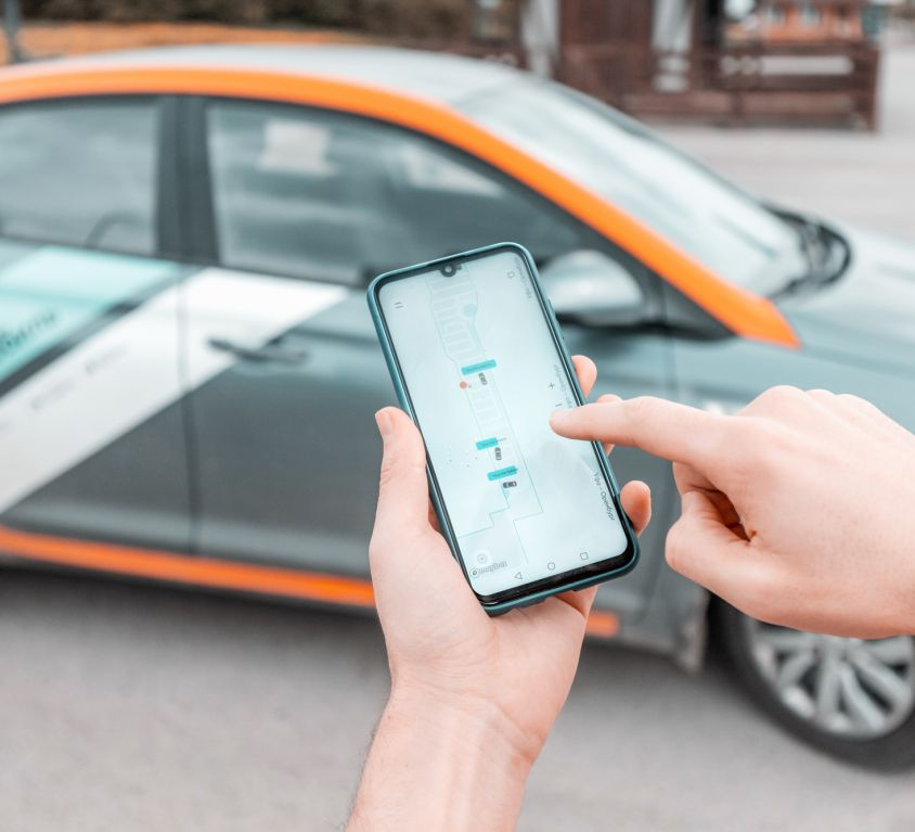 11 May 2020, Ufa, Russia: young person on a smartphone books a car in the Delimobil carsharing app to get around the city. New generation chooses not to own a car but to rent a vehicle